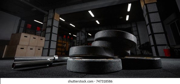 Selective focus on weights and gym equipment on the floor at fitness box weightlifting fitness box training exercising space interior dark brutal motivation determination concept