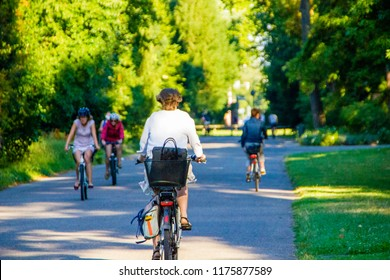 Selective focus on a woman cycling on her bike with many other in the background on a sunny summer day. Driving to work or school with the bike to have a healthy lifestyle