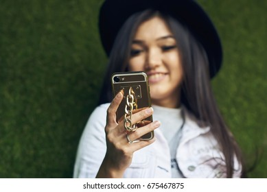 Selective focus on woman hand holding modern mobile phone with stylish phone case.Smiling asian female watching funny video on smartphone.Young positive hipster girl using technology