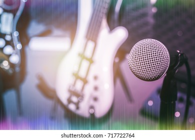 Selective focus one of microphone with the blur of electric bass and guitar.mix variety of instrument on the home music studio recording background concept.Pastel tone and sound wave.