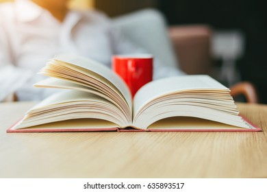 Selective focus open old book with blurred red hot coffee on  wooden table at coffee shop  in the morning