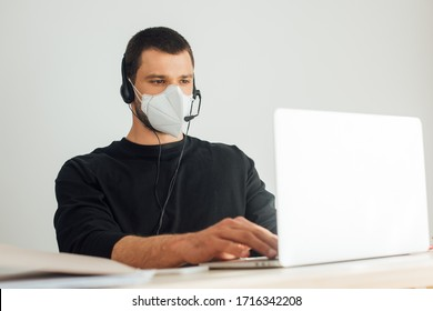 selective focus of operator in medical mask and headset working from home with laptop