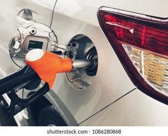 Selective focus orange Fuel nozzle Pumping Gasoline fuel in Car at a pump gas station.
