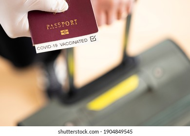 (Selective focus) Overhead view of an human hand wearing a latex glove, holding a passport with 'Covid-19 Vaccinated' label inside it. Travel concept during the Covid-19 pandemic.