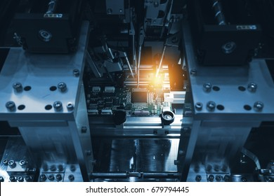 Selective focus to PCB circuit board. Automation of machine industry assembly of computer circuit board in smart factory for production computer components. Blue tone with flare light.
