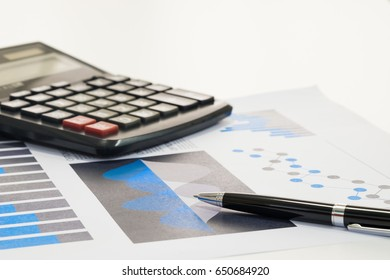 selective focus pen on graph financial and blurred calculator with copy space for finance; accounting; risk; investor; management concept