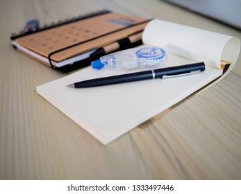 Selective focus pen on notebook with stationary item on wooden desk,eduction concepts.