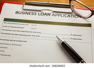 selective focus pen,Business loan application form,glasses ,red paper clip on wood background.