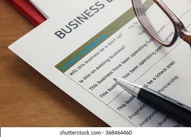 selective focus pen,Business loan application form ,glasses,paper clip on wood background.