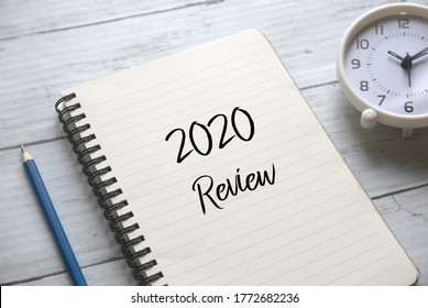 Selective focus of pencil,clock and notebook written with 2020 review on white wooden background.