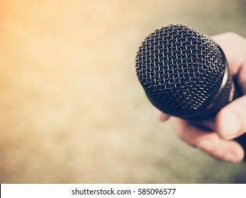 Selective focus photo of black microphone in human hand with blur green background and light . Business conference event or symposium concept . Vintage style and filtered process.