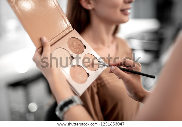 Selective focus photo of make-up artist holding contouring palette while using professional brush