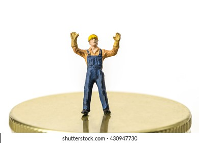selective focus photo of miniature worker man standing on stage on white background,