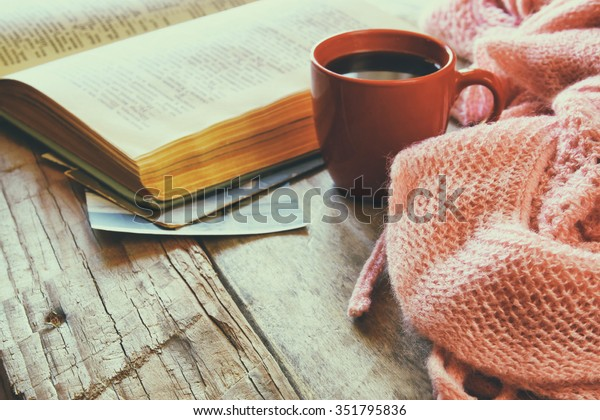 selective focus photo of pink cozy knitted scarf with to cup of coffee and open book on a wooden table. style retro filtered