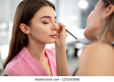 Selective focus photo of professional makeup artist applying shadows for beautiful girl while using special brush