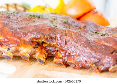 Selective focus point on Grilled rib pork with barbecue sauce and vegetable and frech fries on wooden cutting board