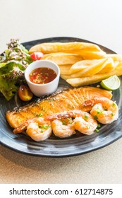 Selective focus point on Grilled salmon and prawn steak in black plate