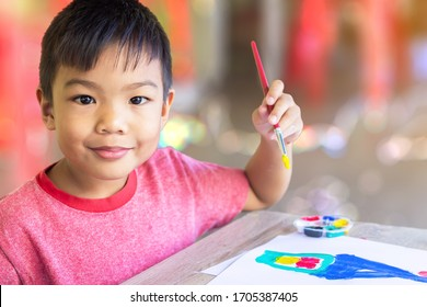 Selective focus. Portrait image of 5 yeas old child boy. Asian student drawing and painting colours on the paper in the room. Study from home, social Distancing, Kid and education concept.