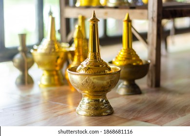 Selective focus of pour water brass with blurred background in temple. Traditional buddhist religious ceremony. Buddhism water libation culture belief after death