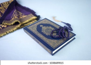 Selective focus of praying mat rug or sajdah or sejadah, wood tasbih and holy Quran with Kurma or Dried Dates Popular During Ramadhan or Fasting Month.