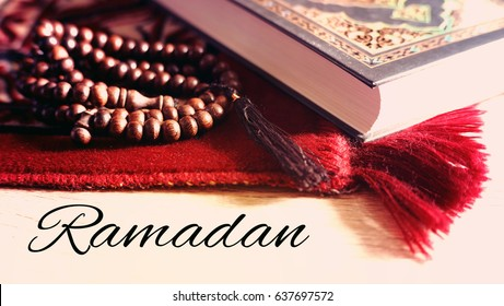 "Selective focus of praying mat rug or sajdah or sejadah, wood tasbih and holy Quran with wording "" Ramadan""."