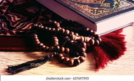 Selective focus of praying mat rug or sajdah or sejadah, wood tasbih and holy Quran.
