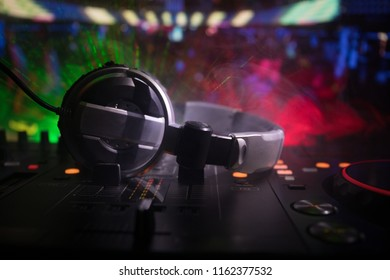 In selective focus of Pro dj controller.The DJ console deejay mixing desk at music party in nightclub with colored disco lights. Close up view