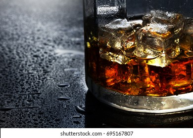 selective focus pure whisky with ice cube inside whisky glass on wet background  alcohol drink concept