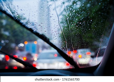 Selective focus to rain droplet with motion blurry wiper on windshield. Motion blurry windshield wipers from inside of car, season rain.