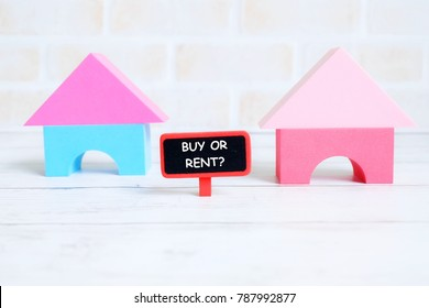 Selective focus of red blackboard written with BUY OR RENT? with house model on white wooden background. Real estate theme.