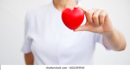 Selective focus of red heart held by female nurse's hand, representing giving all effort to deliver high quality service mind to patient. Professional, Specialist in white uniform isolated on white