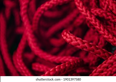 selective focus red rope texture made of fine cotton yarn. soft string strands with crisscross webbing