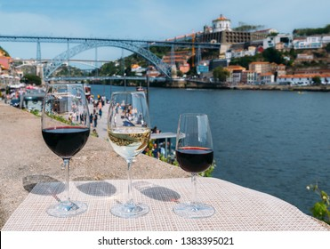 Selective focus of Red, white and Porto wine glasses overlooking Cais da Ribeira and Ponte de Dom Luis I on the River Douro in Porto, Portugal
