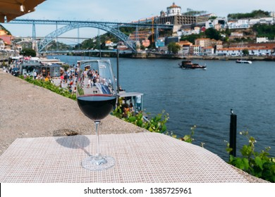 Selective focus of red wine glass overlooking Cais da Ribeira and Ponte de Dom Luis I on the River Douro in Porto, Portugal