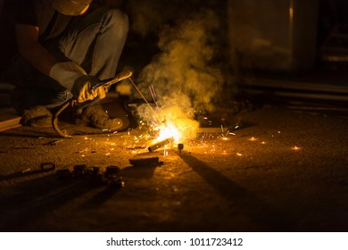 selective focus at right hand and Motion blur. Low light image of Welder or craftsman in a welding mask and welders leathers, a metal product is welded with a welding machine in the garage.