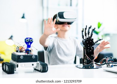 Selective focus of robotic devices standing on the table while ingenious young boy testing them with VR device
