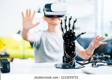 Selective focus of a robotic hand on the table with a little smiling boy testing VR glasses in the background