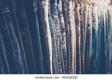 Selective focus row of hanged blue jeans in a shop