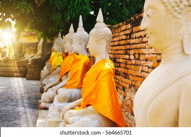 Selective focus, Row of old Buddha Statues with Blue Sky background at Wat Yai Chai Mongkhon Old Temple in Ayutthaya Historical Park Thailand.