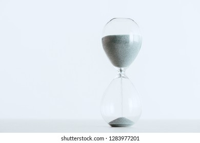 selective focus of running sand in hourglass isolated on white