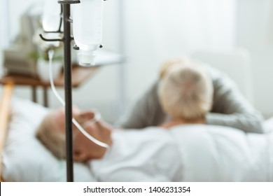 selective focus of sad senior woman with husband in coma in clinic