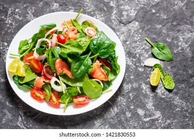 Selective focus Salmon Fresh green Salad with spinach, cherry tomatoes,baby spinach,  Concept for a tasty and healthy meal. Dark stone background. Top view. Close up.