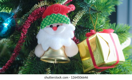 Selective focus of Santa dall Bells and Christmas Gifts box hanging on the tree decorative for christmas holiday.