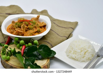 Selective focus Savory curry with pork and Plain jasmine rice in the white dish near the Thai herbs.