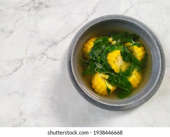 Selective focus of sayur bayam bening or spinach clear soup with corn in grey bowl and white table.