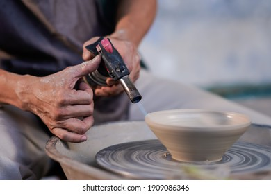 Selective focus sculptor hand using blowtorch. Professional artist worker creating a bowl with wet clay. Image contains certain grain or noise and soft focus.