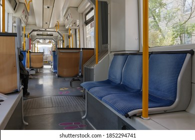 Selective focus at seat and interior view of a corridor inside passenger trains or light rail tram with blue fabric seats of German railway train system. Empty vacant passenger car inside the train.