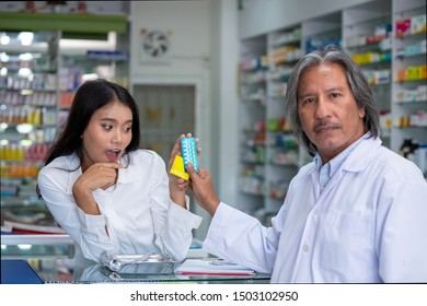 Selective focus of senior asian pharmacist man discussion how to use contraceptive pill and condom to young asian woman at pharmacy drugstore. Pharmacist advice young woman about safe sex.