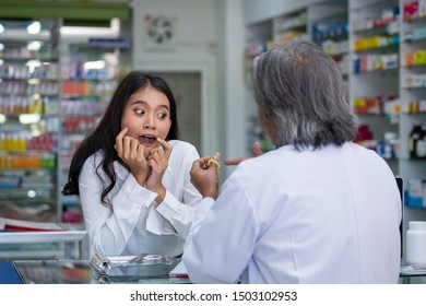 Selective focus of senior asian pharmacist man discussion how to use condom to young asian woman at pharmacy drugstore. Male pharmacist advice young woman about safe sex.