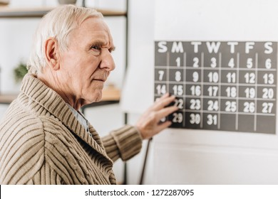 selective focus of senior man touching wall calendar and remembering dates